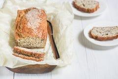 Nytt bakat bröd med sesamfrö på ett träbräde på en lig Royaltyfri Fotografi