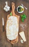 Nytt bakat ciabattabröd med vitlök, medelhavs- oliv, basilika och parmesanost på portion stiger ombord över lantligt Royaltyfri Bild