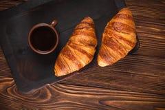 Nytt bakat giffeldriftstopp, kopp kaffe i den vita koppen på brun träbakgrund Franskan frukosterar nya bakelser för frukost royaltyfria foton