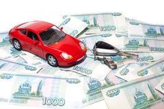 Nytt bilbegrepp - tangent och en röd bil med sedlar royaltyfri bild