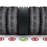 Nytt bilgummihjul med den gröna kontrollfläcken som står ut bland gamla gummihjul Royaltyfri Fotografi