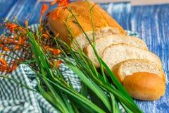 Nytt bröd, blommor på blå träbakgrund och gräsplantyg Royaltyfri Bild
