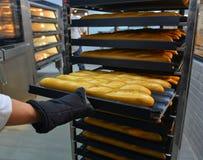 Nytt bröd i en bageriugn arkivfoto