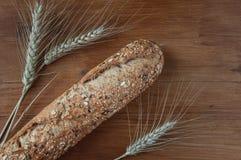 Nytt bröd med frö på den lantliga trätabellen Arkivbild