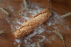 Nytt bröd med frö på den lantliga trätabellen Arkivfoto