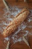 Nytt bröd med frö på den lantliga trätabellen Fotografering för Bildbyråer