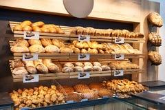 Nytt bröd och bakelser på hyllor i bageri arkivfoto