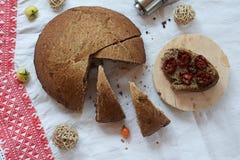 Nytt bröd och sol-torkade tomater på lantlig bordduk Royaltyfria Bilder