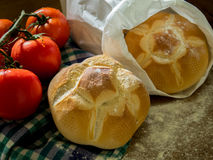 Nytt bröd och tomater på en tabell Arkivbild