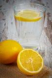 Nytt citron och exponeringsglas av rent vatten med skivan av citronen, kall lemonad arkivbild