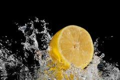 Nytt citronfärgstänkvatten Isolerat på spegelsvartbakgrund arkivfoton