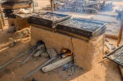 Nytt coughtfisk som rökas över den traditionella leraugnen på kusten av Ghana, Västafrika arkivbilder