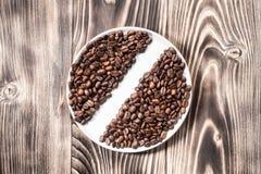 Nytt för kaffebönor som grillas i rund bunke på en trätabell Arkivbild