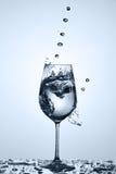 Nytt genomskinligt vatten som häller med vatten, bubblar i ett glass anseende på exponeringsglaset mot ljus bakgrund Arkivbilder