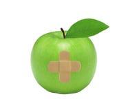 Nytt grönt äpple med den medicinska lappen som isoleras på vit Arkivfoton