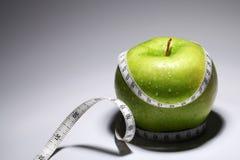 Nytt grönt äpple med måttbandet Royaltyfri Bild