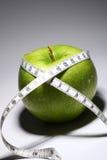 Nytt grönt äpple med måttbandet Arkivfoto
