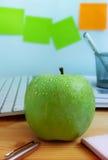 Nytt grönt äpple på kontorsskrivbordet Royaltyfri Foto