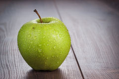 Nytt grönt äpple på tabellen Royaltyfria Foton