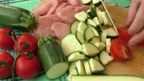 Nytt griskött på skärbrädan klipps in i stycken med grönsaker arkivfilmer