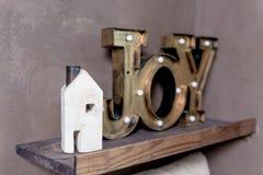 Nytt hem- begrepp för litet trähus Formuleringar för textmeddelande av ordet GLÄDJE i mitt nya hus Låtna drömmar att komma riktig arkivfoto