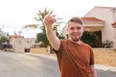 Nytt hem-, lägenhet-, ägare- och folkbegrepp - som är nära upp av tangenter den unga lyckliga man för visning med det nya hemmet  Arkivbilder