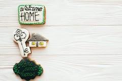 Nytt hus för inflyttning, välkommen hem- uppsättning Tangenten huset, kakor för välkommet tecken på vitt trä, lägger framlänges m arkivfoton