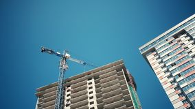 Nytt hus i ett nytt bostads- komplex Konstruktionsprocess av skyskrapan och nya lägenheter med kranar på en blå himmel stock video