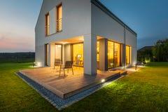 Nytt hus som är upplyst på natten arkivfoto