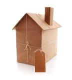 Nytt hus som slås in i brunt papper Arkivfoto