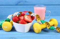 Nytt jordgubbar, milkshake, hantlar och cm på blåa bräden, begrepp av den sunda och sportiga livsstilen Royaltyfria Bilder