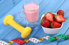 Nytt jordgubbar, milkshake, hantlar och cm på blåa bräden, begrepp av den sunda och sportiga livsstilen Royaltyfri Bild