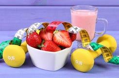 Nytt jordgubbar, milkshake, hantlar och cm på sund och sportig livsstilen den bräden, Royaltyfria Bilder