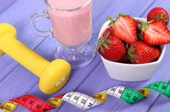 Nytt jordgubbar, milkshake, hantlar och cm på sund och sportig livsstilen den bräden, Arkivbilder