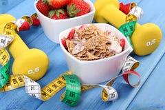 Nytt jordgubbar, vete- och rågflingor, hantlar och cm, sunt livsstilbegrepp Arkivfoto