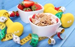 Nytt jordgubbar, vete- och rågflingor, hantlar och cm, begrepp av den sunda och sportiga livsstilen Arkivfoton