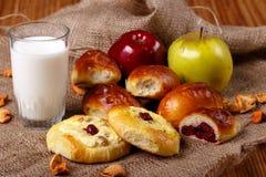 Nytt körsbärsrött pajer, tarts, äpplen och exponeringsglas av mjölkar Arkivbild