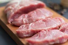 Nytt kött med kryddor på skärbrädan för kotletter royaltyfri fotografi