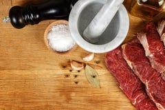 Nytt kött med kryddor på träbräde arkivfoton