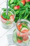Nytt kallt ingett Detoxvatten med mogna organiska jordgubbar skivade gurkamintkaramellen i exponeringsglas och tillbringare Vit p Arkivbild