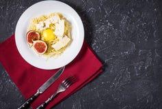 Nytt lagad mat pasta med fikonträd, äggula, ost som dekoreras med servetten över ett lantligt stenbräde Top beskådar kopiera avst Arkivfoto
