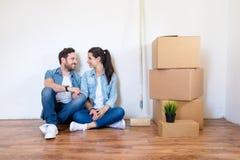 Nytt liv för lyckliga par som sitter på golv med många askar arkivbilder