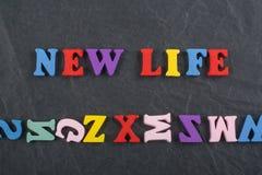 NYTT LIVord på svart brädebakgrund som komponeras från träbokstäver för färgrikt abc-alfabetkvarter, kopieringsutrymme för annons arkivfoton
