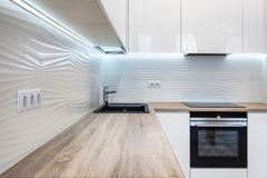 Nytt ljust modernt kök med byggt i ugns- och kromvattenklapp och en trätabellöverkant Arkivfoto