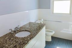Nytt modernt badrum med beigategelplattor och det bruna kabinettet Fotografering för Bildbyråer