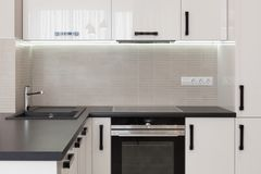 Nytt modernt kök med byggt i ugns- och kromvattenklapp Arkivfoto