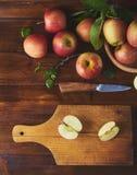 Nytt moget äpple i bunke, skärbräda med kniven och halva av royaltyfri fotografi