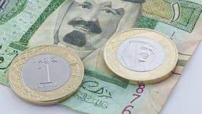 Nytt mynt för saudierRiyal med konungen Salman VS gammal sedel med Previ Arkivbild