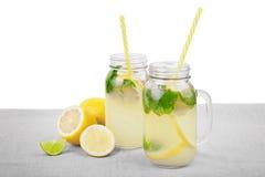 Nytt och mång--färgade drinkar med mogna, saftiga och nya citroner, mintkaramell, vatten på ett ljust tyg som isoleras på en vit  Royaltyfri Fotografi