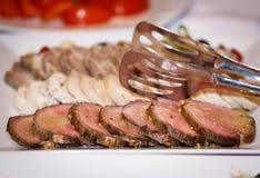 Nytt och rått kött Ländstyckemedaljongbiffar i rad som är klara att laga mat Svart svart tavla för bakgrund royaltyfri bild